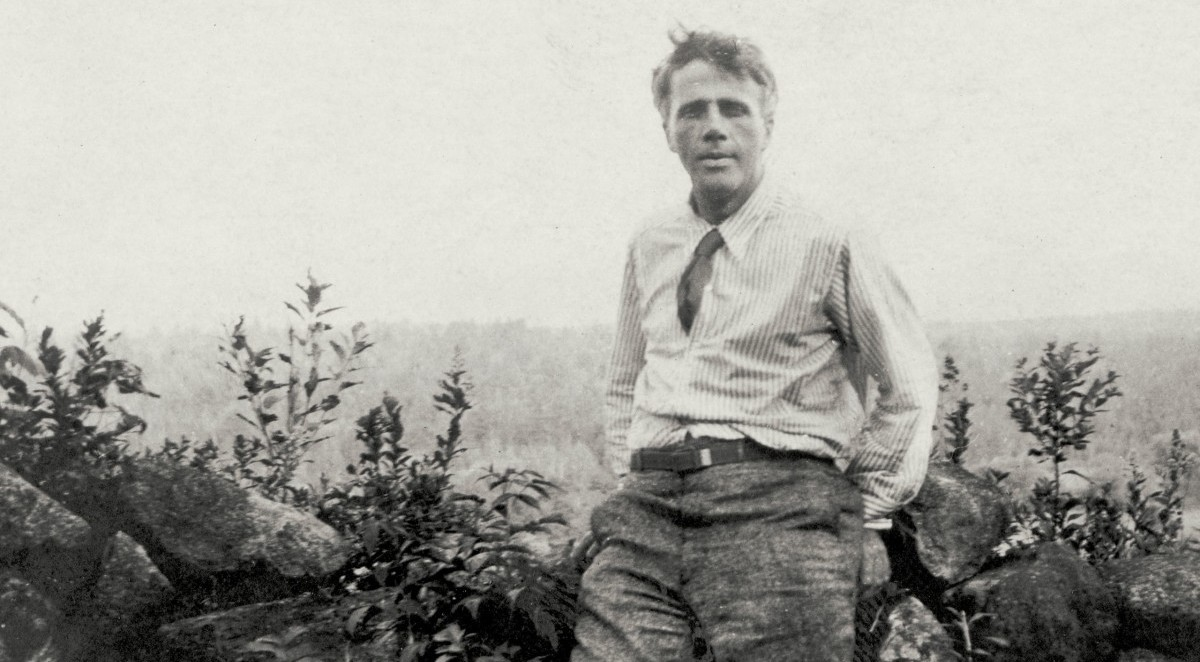 Robert Frost sitting on a recently-mended wall.
